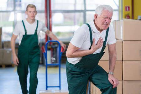 ataque al corazón: Empleado mayor que tiene ataque al corazón en el lugar de trabajo Foto de archivo