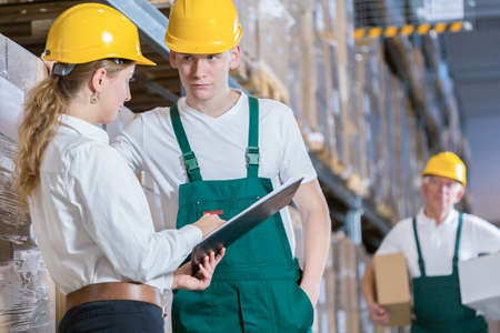 supervision: Manager talking with storage worker in warehouse Stock Photo