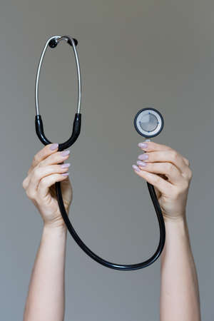 Vertical view of female hands with stethoscope