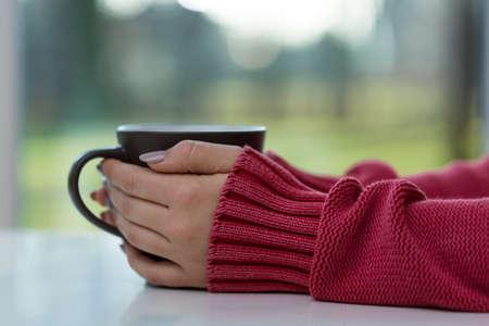 Horizontale mening van de vrouw het drinken van hete thee