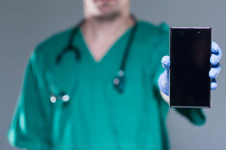View of male doctor with mobile phone
