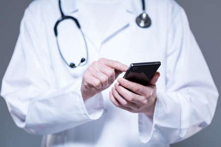 水平の携帯電話を使って、手を男性医師