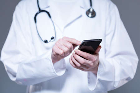 Male doctor hands using mobile phone, horizontal