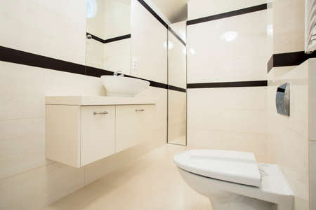 a toilet seat: Interior of toilet with beige and black tiles Stock Photo