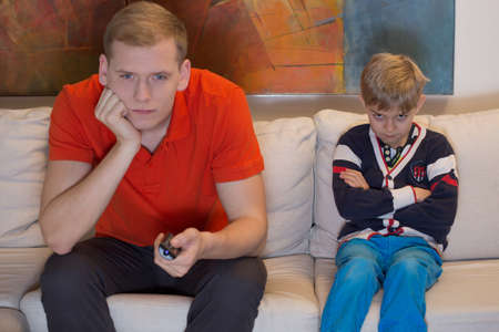 Immature dad watching tv and his bored son photo