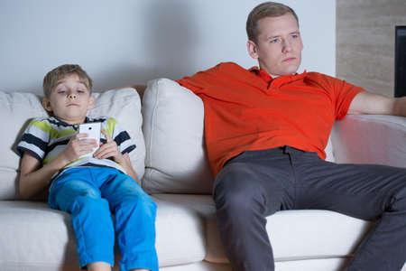 gente viendo television: Ni�o sentado en el sof� y el uso de tel�fonos inteligentes Foto de archivo