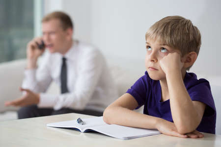 workaholic: Close-up of bored child sitting at the desk Stock Photo