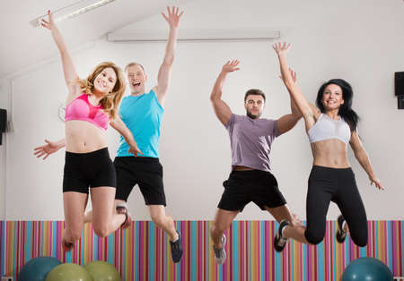 air jump: Happy fit people jumping at the gym