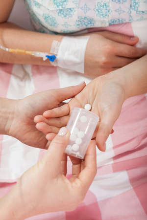 bedridden: Close-up of nurses hands giving patient pills