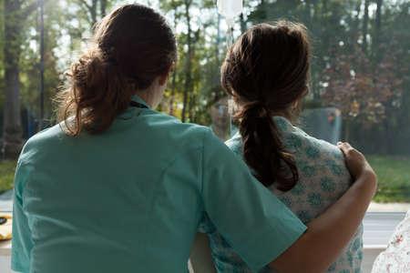 Una enfermera cuida triste paciente en el hospital Foto de archivo