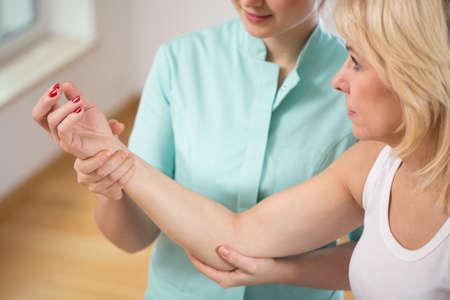 fisioterapia: Fisioterapeuta joven que dobla el codo de la mujer Foto de archivo