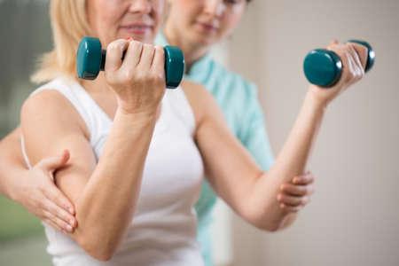 fisioterapia: Mujer que ejercita con pesas en clínica de rehabilitación Foto de archivo