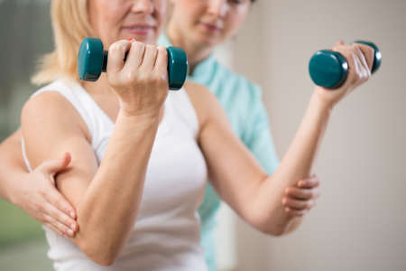 Woman exercising with dumbbells in rehabilitation clinic