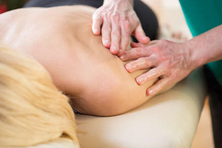 spinal manipulation: Close-up of masseur stroking the skin of young woman