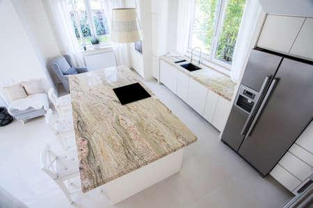 明るいキッチン、垂直で大きな花崗岩のワークトップ