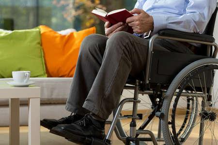 Крупным планом человека, используя инвалидной коляске чтение книги