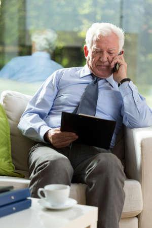 Elderly elegant businessman sitting in armchair