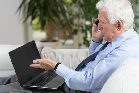Senior businessman using laptop and talking on the phone photo