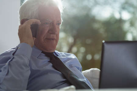 Elegant businessman with grey hair during work photo
