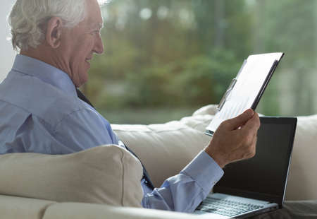 Portrait of retired businessman analyzing business columns photo