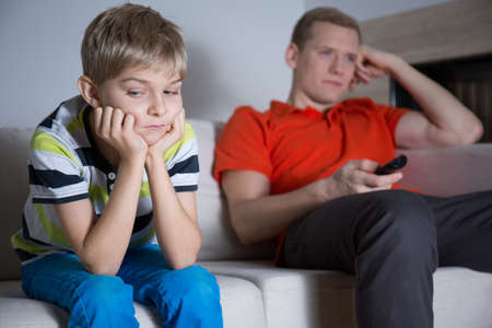 Bored child sitting on the sofa and his father watching tv Stock Photo