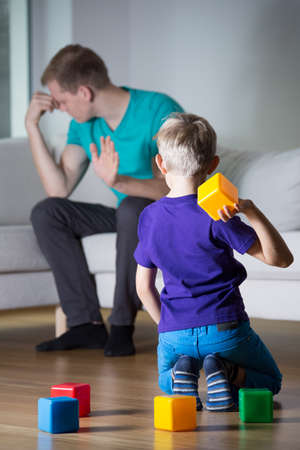 wants: Young dad having headache and his son wants to play Stock Photo