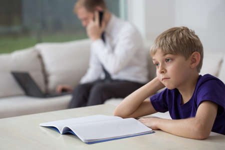 workaholic: Dad working at home and bored son doing homework