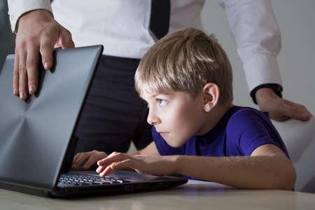 enfant qui joue: Papa ne permettent pas le fils en utilisant son ordinateur portable