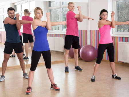 Young people training together in fitness center