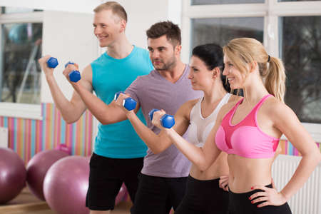 Fit athletic people working out with dumbbells