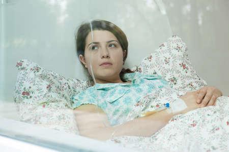病院のベッドで横になっている病気の若い女性