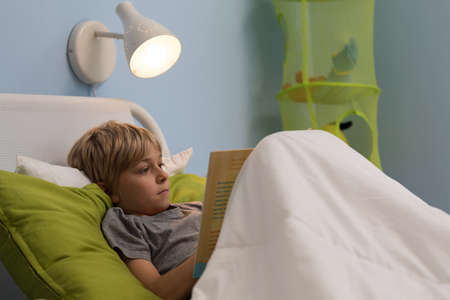 child in bed: Little worried boy sitting alone in his hospital bed Stock Photo