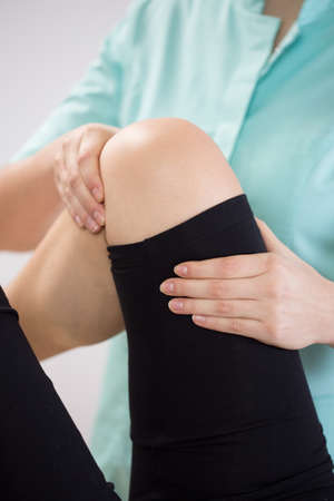 calf pain: Close-up of therapist flexing patients knee