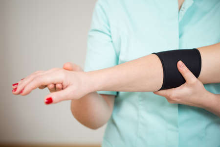 elbow band: Close-up of womans sick arm with protective band Stock Photo