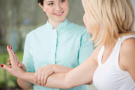 Jonge fysiotherapeut en pols van haar patiënt oefening