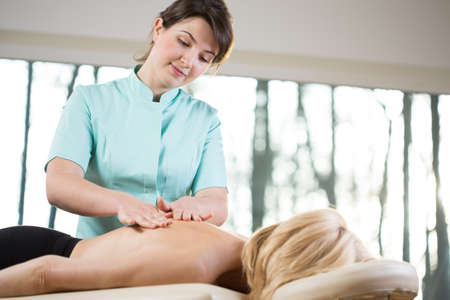 spinal manipulation: Young female physiotherapist doing the massage to her patient Stock Photo