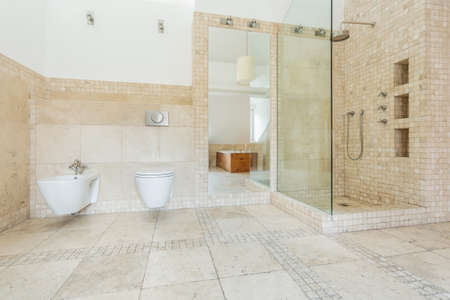 bathroom tile: Bathroom with beige tiles on the wall