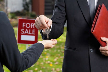 sales agent: Real estate agent giving the keys to the buyer