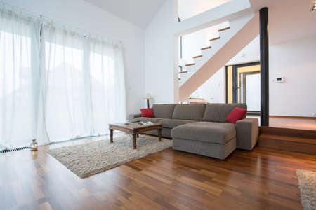 single rooms: Wooden parquet and small carpet in living room Stock Photo