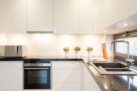 llave de agua: Primer plano de un mueble de cocina blanco en un interior moderno