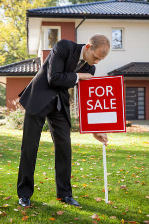 selling house: Young real state agent selling big house Stock Photo
