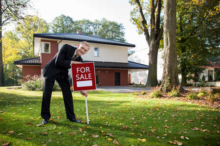 Jonge knappe releator in de voorkant van het huis te koop