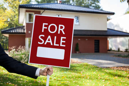 real estate agency: Close-up of real estate agent holding for sale sign Stock Photo