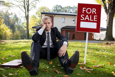 vendedor: Preocupado agente de bienes raíces y la casa en venta