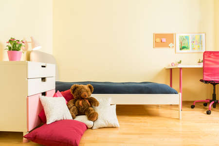 Cute children mascot on colorful pillows in bedroom Banque d'images