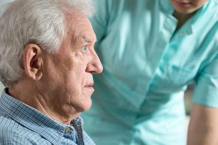 Close-up of elderly worried sick man sitting with nurse
