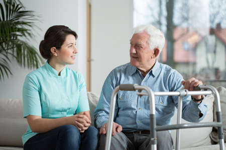 dos personas hablando: Ancianos reuni�n enfermo con su enfermera muy joven Foto de archivo