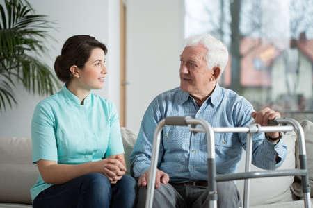 Bejaarde zieke man vergadering met zijn jonge mooie verpleegster