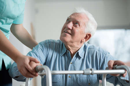 an elderly person: Close-up of aged man trying to stand up with walker Stock Photo
