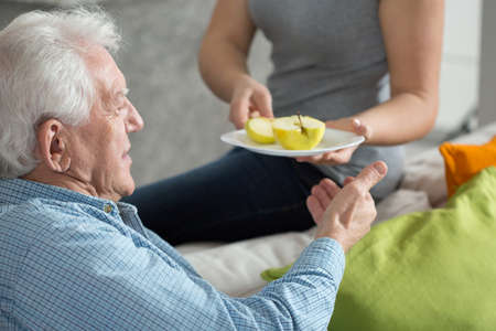 Elderly man eating fruit for dessert Stockfoto